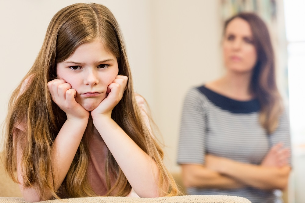 daughter sitting upset with her mother living room