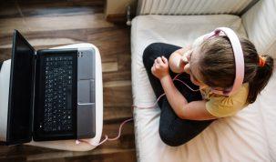 girl headphones wathcing movie laptop
