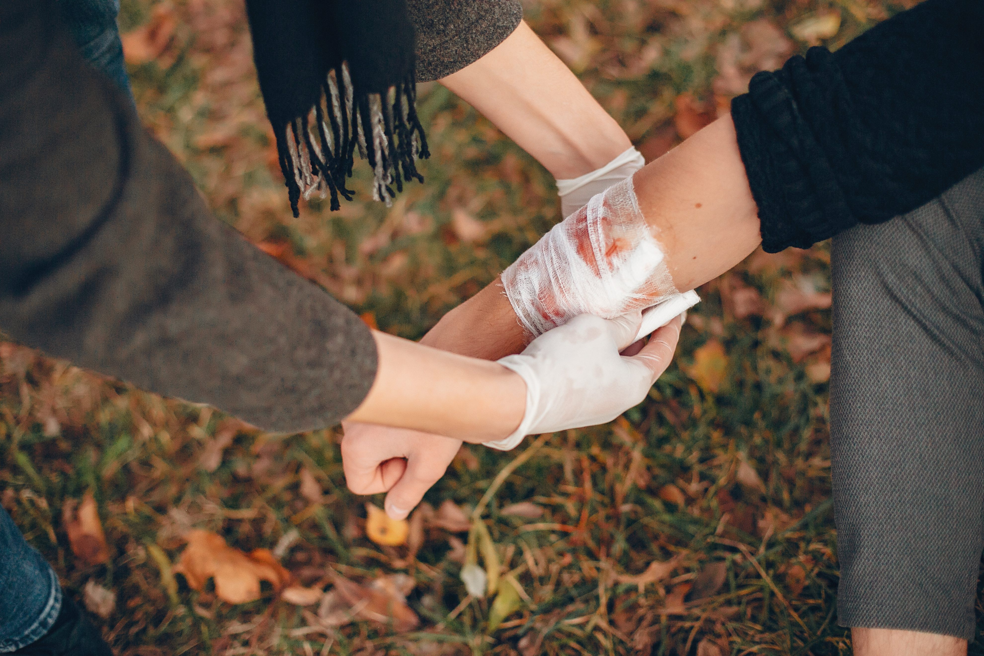 providing first aid park man bandaged injured arm guy helps friend