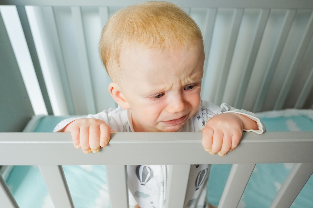 worried cute baby standing crib holding railing crying looking away closeup shot high angle child care childhood concept